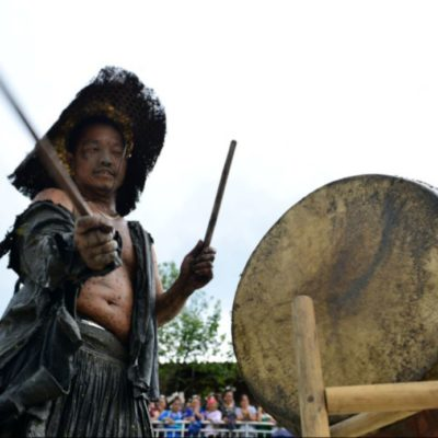"""One of the Miao people playing  a drum on """"Dog Carrying Day"""""""