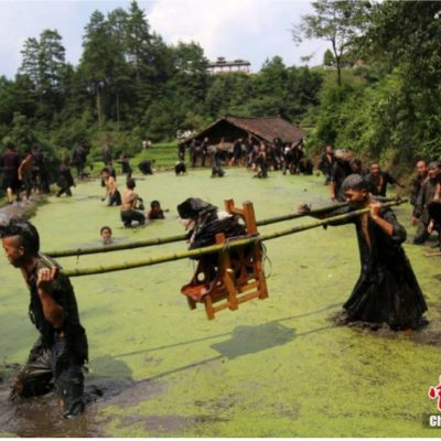 """Miao people carrying a dog in a caravan for """"Dog Carrying Day"""""""